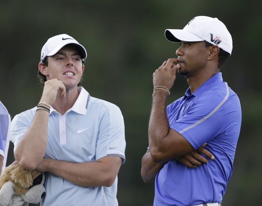 FILE - In this June 13, 2013, file photo, Rory McIlroy, left, and Tiger Woods stand together during the first round of the U.S. Open golf tournament at Merion Golf Club in Ardmore, Pa. Anyone could see McIlroy had the gifts to be the next big thing in golf. His victory in the PGA Championship was more about grit. And now the comparisons with Woods are becoming inevitable. (AP Photo/Darron Cummings, File)