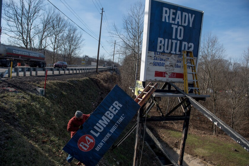 Steve Greenawalt works on a billboard for 84 Lumber in Eighty Four, Pa. on Monday.