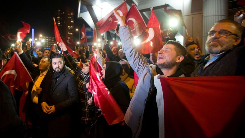 Demonstrators wave Turkish flags outside the Turkish consulate in Rotterdam, Netherlands, Saturday, March 11, 2017.