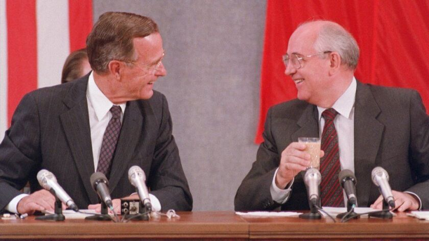 President George H.W. Bush and his Soviet counterpart Mikhail Gorbachev laugh during a joint news conference in Moscow on July 31, 1991.