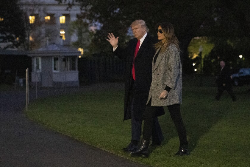 President Donald Trump and first lady Melania Trump walk on the South Lawn of the White House in Washington, Tuesday, Nov. 12, 2019, after stepping off Marine One as they return from New York. (AP Photo/Patrick Semansky)