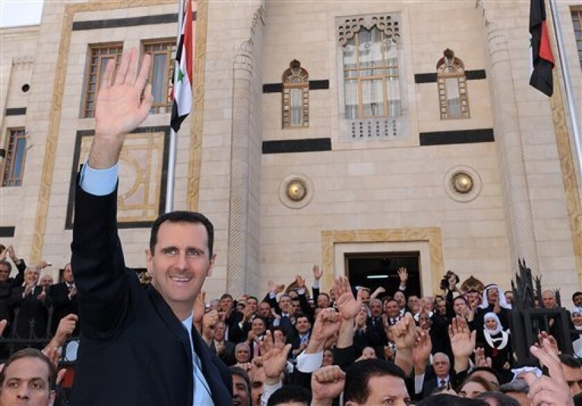 In this photo released by the Syrian official news agency SANA, Syrian President Bashar Assad, left, waves to his supporters after he made a speech at the Parliament, in Damascus, Syria, Wednesday, March 30, 2011. Syria's president has blamed the wave of protests against his authoritarian rule on 'conspirators' - but he failed to offer any concessions to appease the extraordinary wave of dissent. (AP Photo/SANA) EDITORIAL USE ONLY
