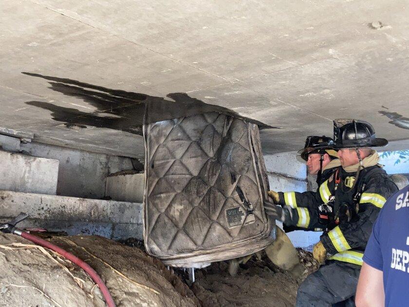 Sacramento firefighters remove a mattress from underneath an overpass on Highway 160.