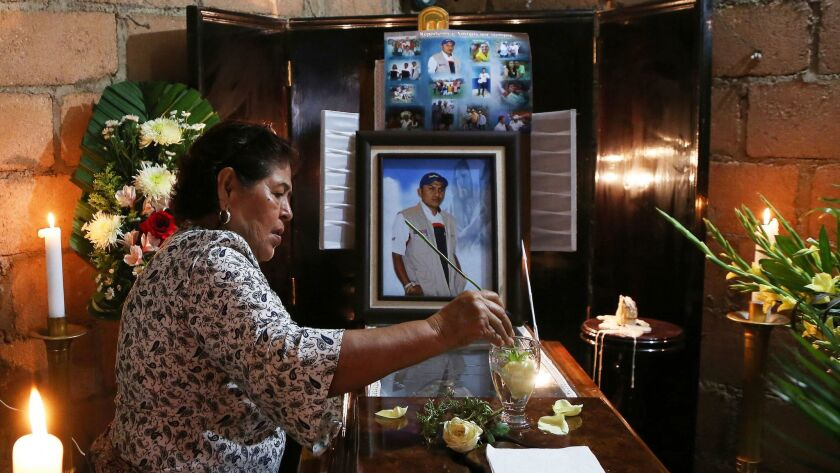 A woman dips a flower in a glass of water placed on the coffin of slain journalist Gumaro Perez duri