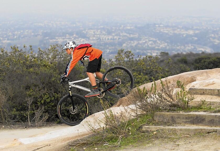 Tai Diggins rides down a slope during practice in the Laguna Beach mountain bike class at Alta Laguna park.