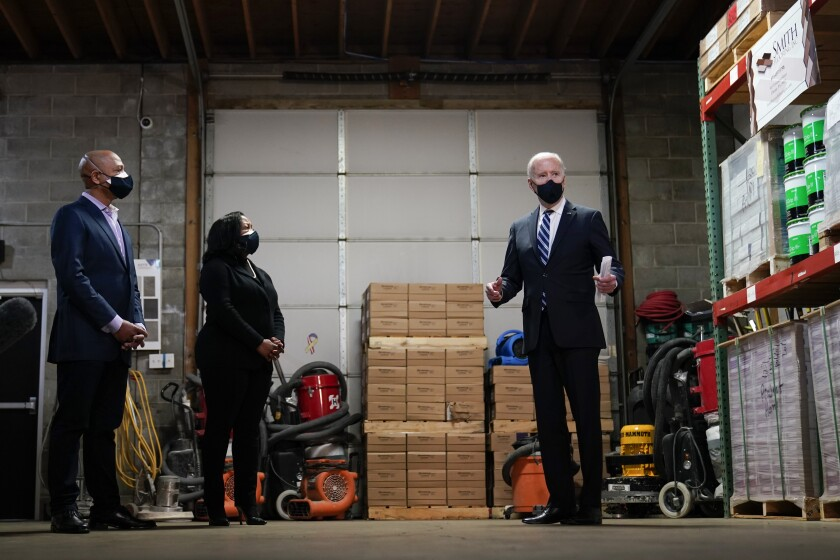 President Joe Biden speaks with owners Kristin Smith and James Smith as he visits Smith Flooring in Chester, Pa., Tuesday, March 16, 2021. (AP Photo/Carolyn Kaster)