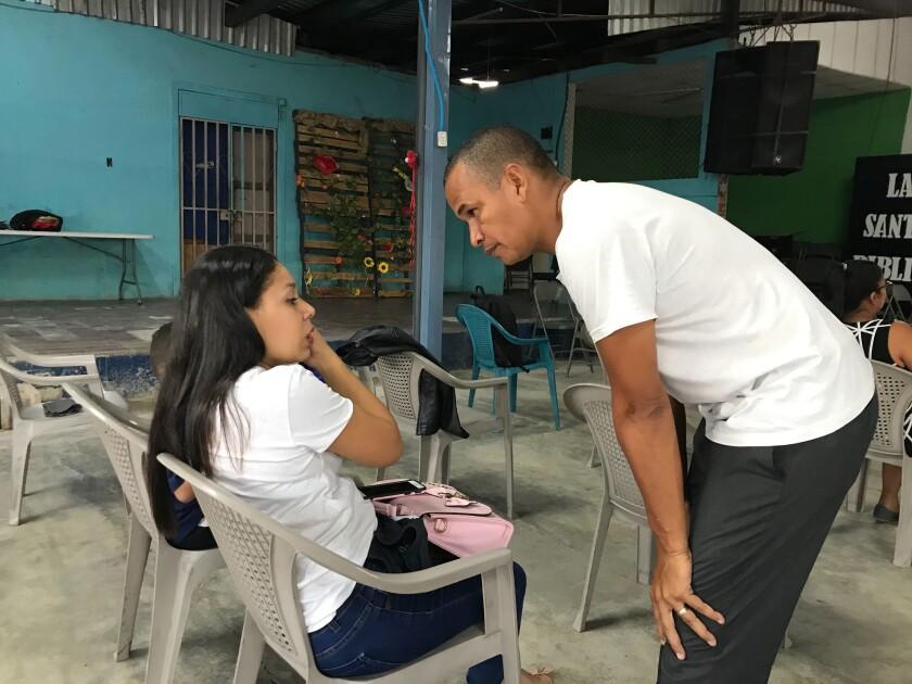 Pastor Pedro González talks with a woman.