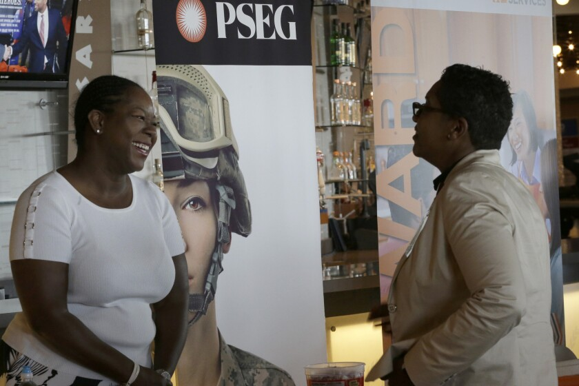 Sophia Lewis, left, with PSEG Long Island, speaks to an attendee at a Citi Field job fair in New York on June 30.