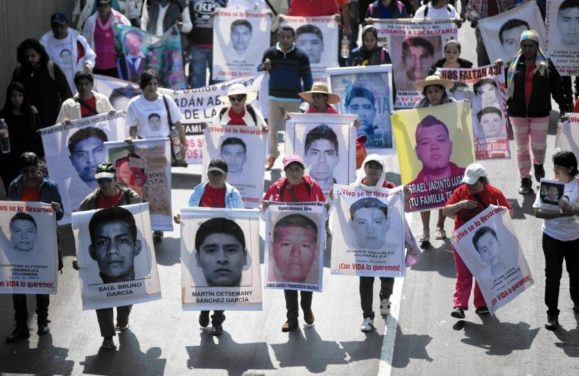 Protesters last month carry photos of some of the 43 college students who disappeared in the Mexican state of Guerrero in September.
