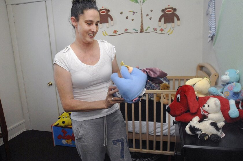 In this Sept. 23, 2014, photo, Amanda Ware arranges stuffed animals for her son, who has never occupied the nursery, in her apartment, in Chicago. In 2003, Ware, then Amanda Hamm, served five years in prison for watching her boyfriend carry out his plot to drown her children, because they interfere