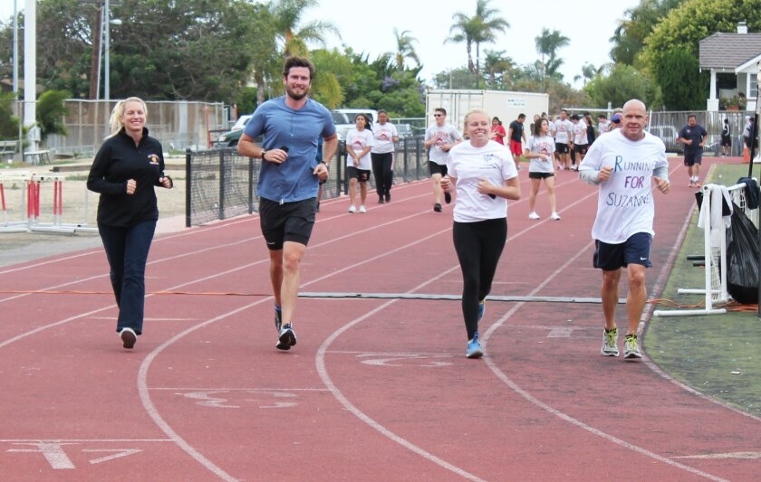 Utahna Atwell, Shane McCoy and Lexi and Tom Atwell run a lap around the La Jolla High School track during the Teens for a Cure event organized by Lexi, whose parents, Tom and Utahna, are both cancer survivors. McCoy, a former La Jolla High student, recently lost his mother to cancer.