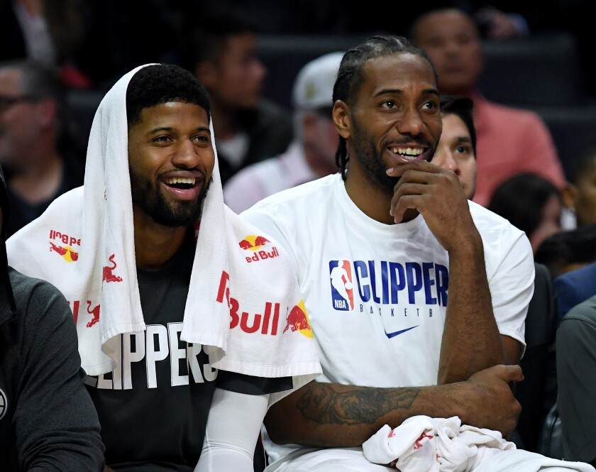 Clippers forwards Paul George, left, and Kawhi Leonard watch their teammates finish off a 120-99 victory over the Phoenix Suns on Dec. 17, 2019, at Staples Center.