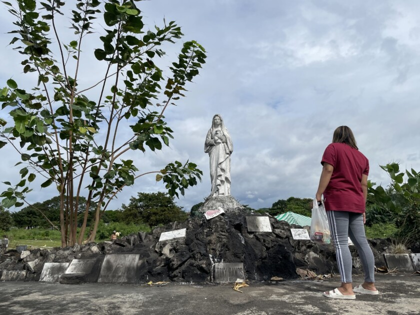 A woman stands in front of a statue at a cemetery