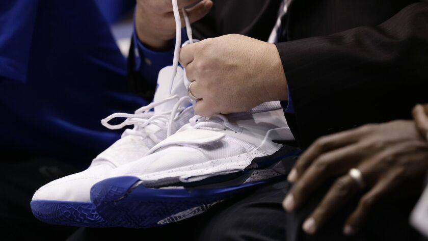 A trainer holds Duke's Zion Williamson's shoes after Williamson left the game against North Carolina due to an injury.