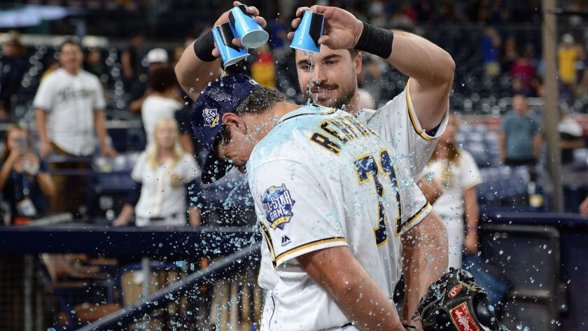 Padres right fielder Hunter Renfroe (71) stands still as catcher Austin Hedges (18) pours Powerade over his head after dodging Hedges' first attempt at dousing him following a 7-1 win over the Los Angeles Dodgers at Petco Park.