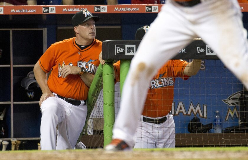Miami Marlins manager Mike Redmond stands in the dugout during the ninth inning of a baseball game against the Atlanta Braves in Miami, Sunday, May 17, 2015. The Braves won 6-0. Redmond was fired Sunday as manager of the Marlins, moments after they were nearly no-hit in a loss that completed a thre