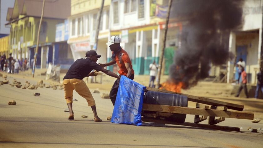 Protesters set up a barricade in the Eastern Congolese town of Beni Thursday Dec. 27, 2018. Police i