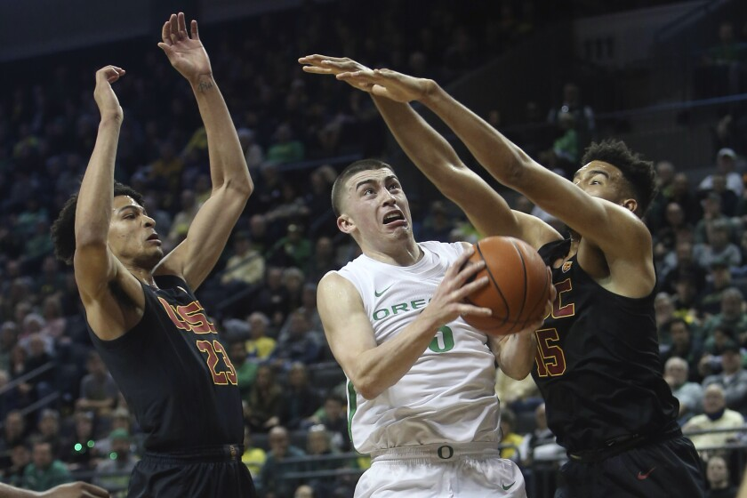 Oregon's Payton Pritchard, center, goes up for a shot between USC's Max Agbonkpolo, left, and Isaiah Mobley, right, during the first half on Thursday in Eugene, Ore.