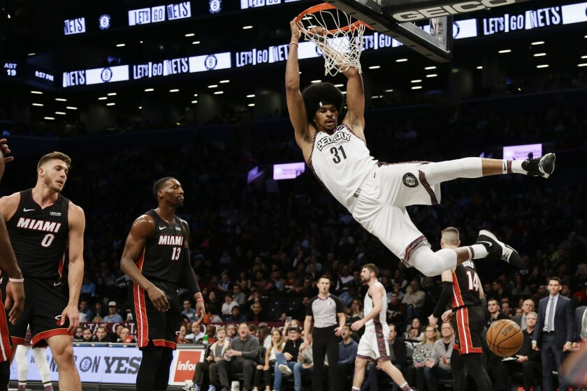 Brooklyn Nets' Jarrett Allen (31) dunks in front of Miami Heat's Bam Adebayo (13), Meyers Leonard (0) and Tyler Herro (14) during the second half of an NBA basketball game Friday, Jan. 10, 2020, in New York. The Nets won 117-113. (AP Photo/Frank Franklin II)