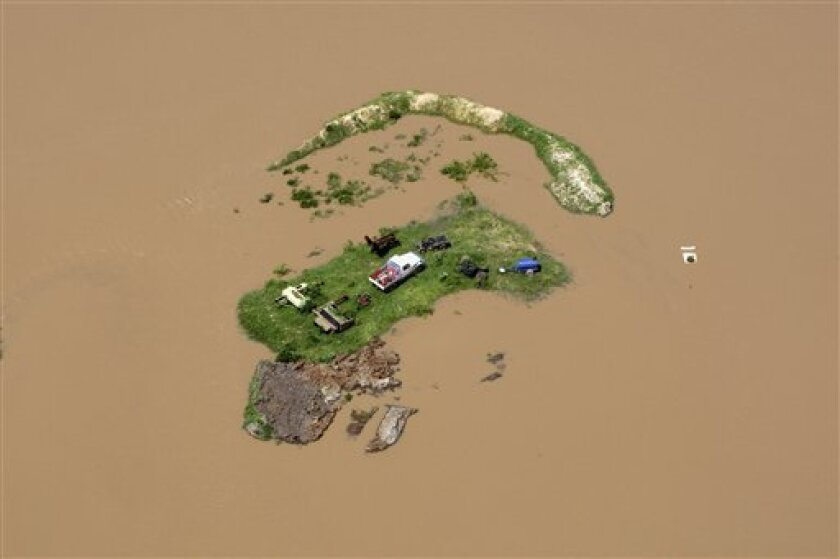 In this Tuesday, Jan. 4, 2011 photo, an island is formed by flood water stranding vehicles and other equipment in Rockhampton, Australia. Floods that have cut air, rail and road links to an Australian coastal city are now threatening its sewage plant, and waters are still expected to rise another few feet before peaking Wednesday. (AP Photo/Janie Barrett, Pool)