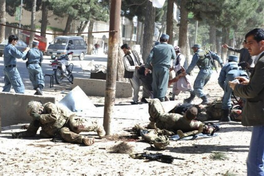 Wounded U.S. soldiers lie on the ground at the scene of a suicide attack in Maimanah, the capital of Faryab province north of Kabul, Afghanistan on Wednesday, April 4, 2012. A suicide bomber blew himself up, killing at least 10 people, including three NATO service members, officials said, the latest in a string of attacks as spring fighting season gets under way. A senior U.S. defense official has confirmed that two U.S. soldiers were among three NATO forces killed in a suicide bombing in northern Afghanistan.(AP Photo/Gul Buddin Elham)