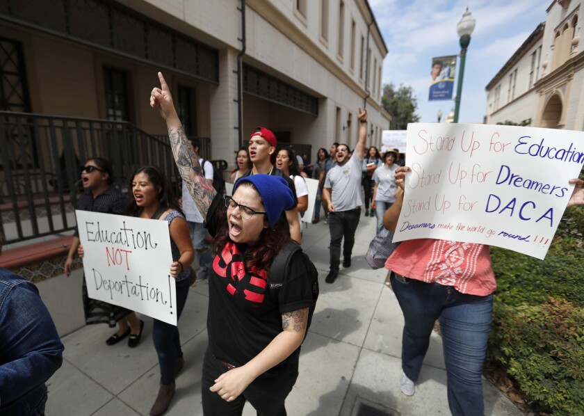 Liz Sanchez, center, a graduate student at Cal State Fullerton, joins students marching around the F
