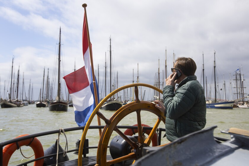 Nearly 200 historic Dutch ships sailed in a flotilla to the fortress island of Pampus, east of Amsterdam, Netherlands, Tuesday, June 9, 2020, to protest against the economic hardship they face from a lack of paying guests after COVID-19 coronavirus restrictions took the wind out of their sails. Pampus island was chosen as location for Tuesday's waterborne demonstration because of a Dutch saying, translated as anchored at Pampus, that means exhausted.(AP Photo/Peter Dejong)