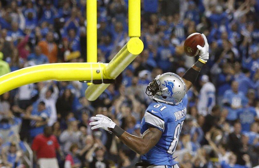 Detroit Lions wide receiver Calvin Johnson (81) prepares to dunk the football after his 20-yard touchdown run during the third quarter of an NFL football game against the Green Bay Packers at Ford Field in Detroit, Thursday, Nov. 28, 2013. (AP Photo/Rick Osentoski)