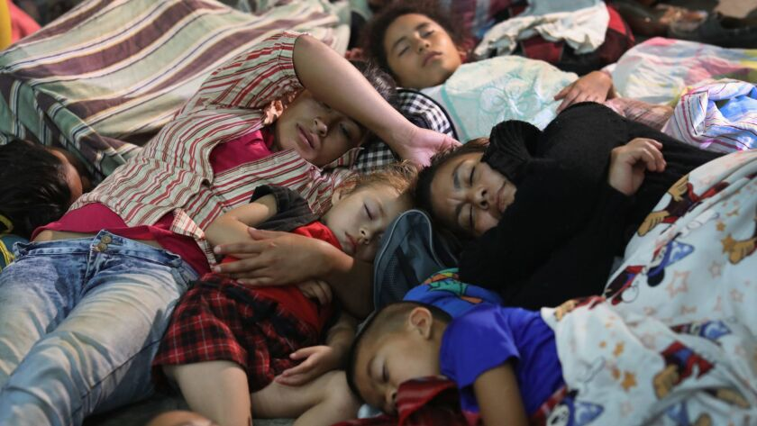 Families of immigrants, part of a migrant caravan of more than 1,500 people, rest for the night in a community gym on Tuesday in Chiquimula, Guatemala.