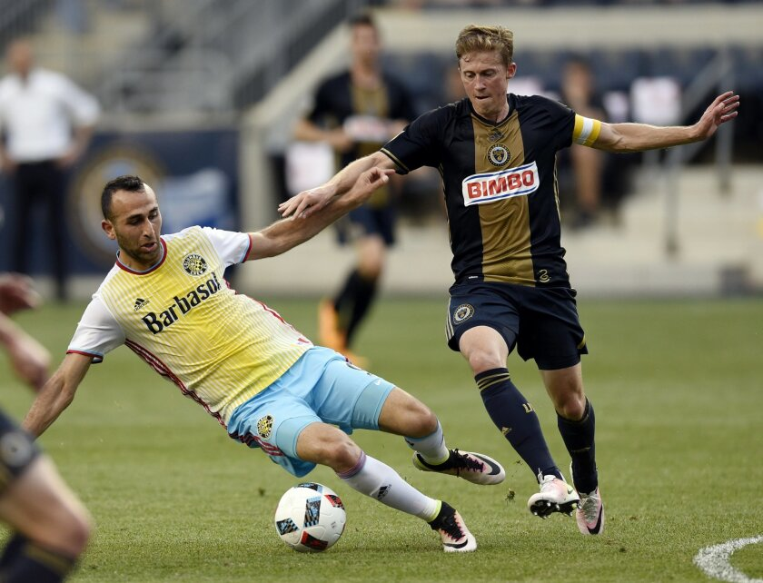 Columbus Crew's Justin Meram, left, gets the ball taken away from Philadelphia Union's Brian Carroll during the first half of an MLS soccer match on Wednesday, June 1, 2016, in Chester, Pa. (AP Photo/Michael Perez)