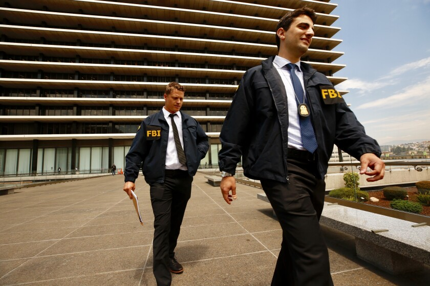 FBI agents leave the downtown headquarters of the Los Angeles Department of Water and Power after serving a search warrant