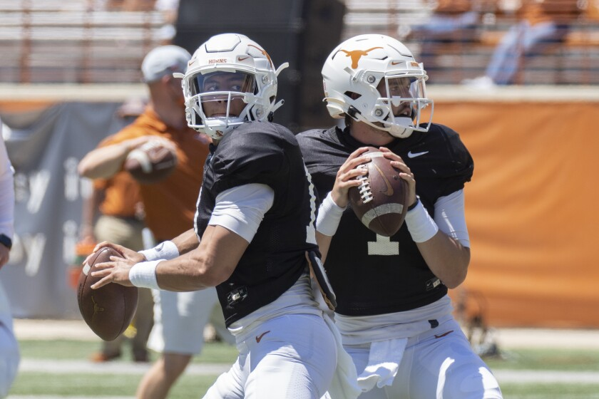 FILE - In this April 24, 2021, file photo, Texas quarterbacks Casey Thompson, left, and Hudson Card warm up before the Texas Orange and White Spring NCAA college football game in Austin, Texas. First-year Texas coach Steve Sarkisian is already shuffling starters, replacing inconsistent redshirt freshman Hudson Card with junior Casey Thompson with the Longhorns already unranked. (AP Photo/Michael Thomas, File)