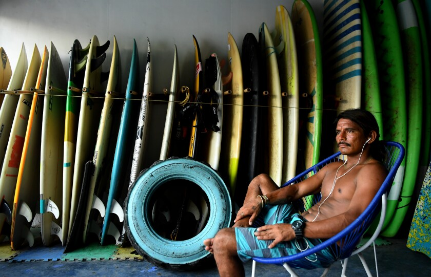 a man sits with surfboards behind him