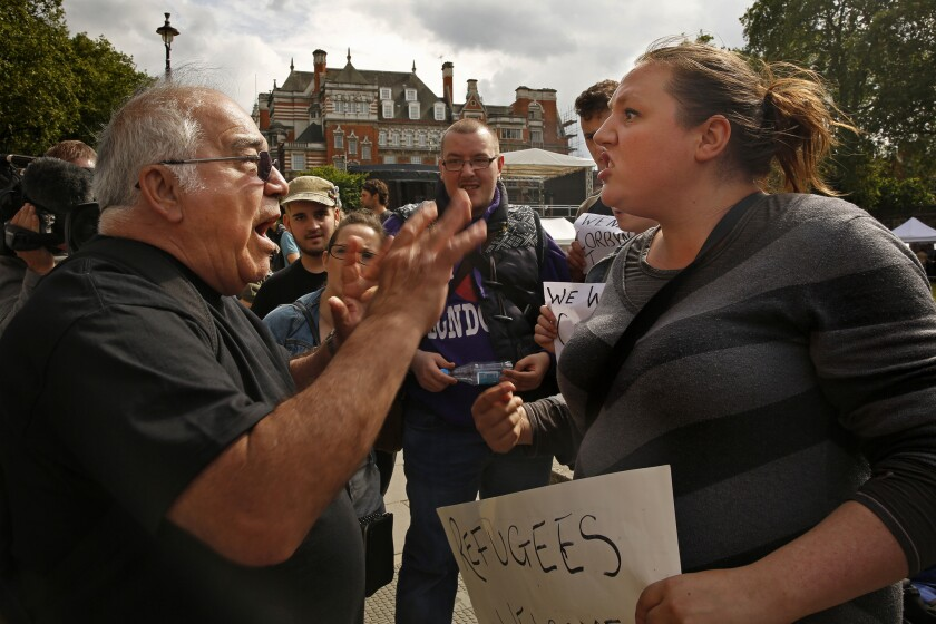 Cara Rose, right, argues over the issue of migrants and immigration with a man on the sidewalk across the street from Parliament in London. Tensions ran high after the historic vote to leave the European Union.