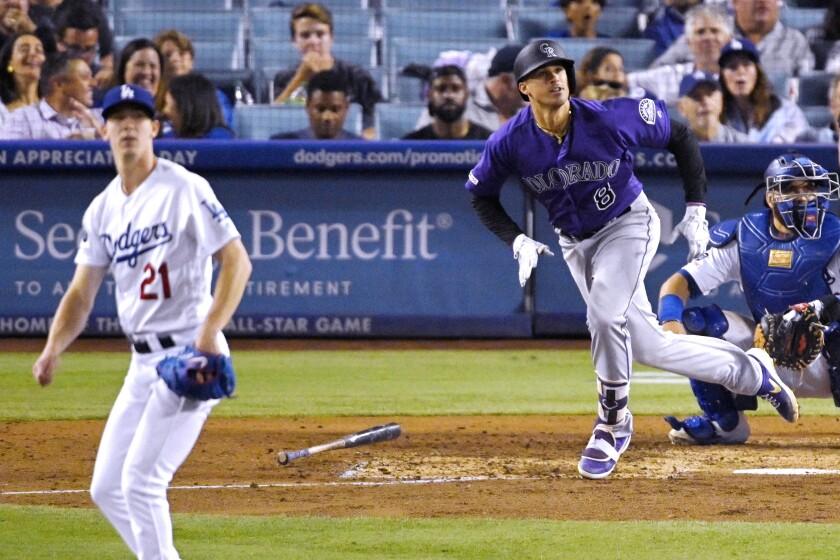 Colorado's Josh Fuentes, center, hits a solo home run off Dodgers pitcher Walker Buehler.