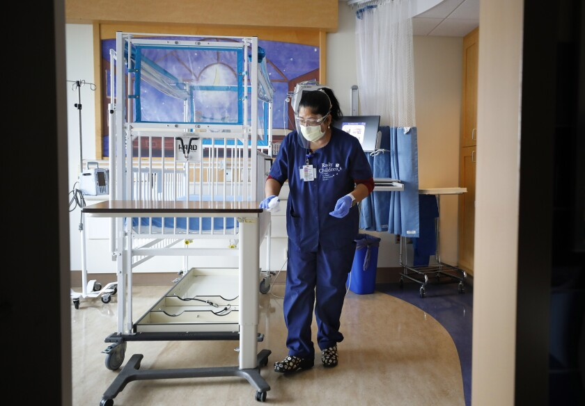 A woman in blue scrubs cleans a hospital room