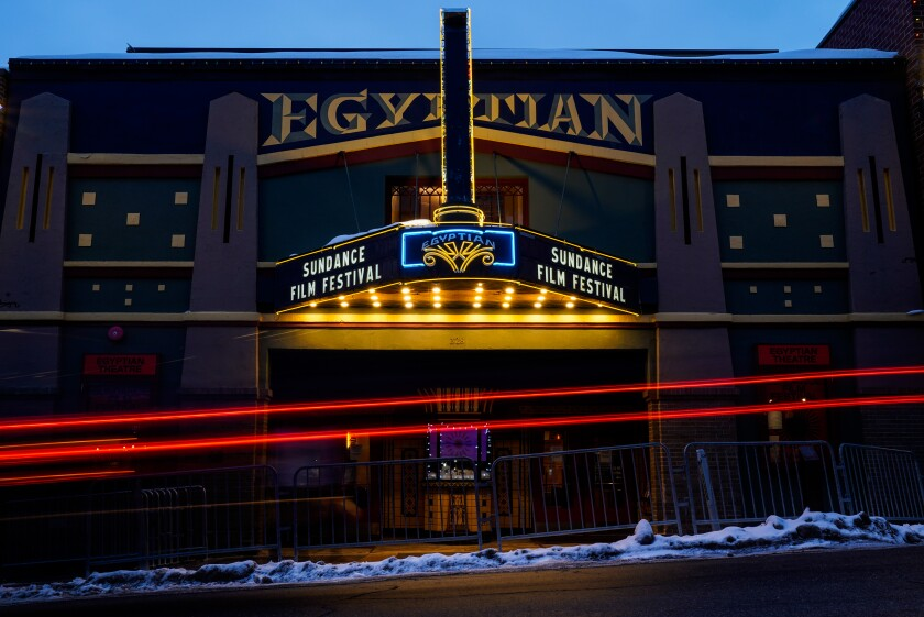 """Snow lines a curb and red beams indicate a passing car at the Egyptian. The marquee reads """"Sundance Film Festival."""""""