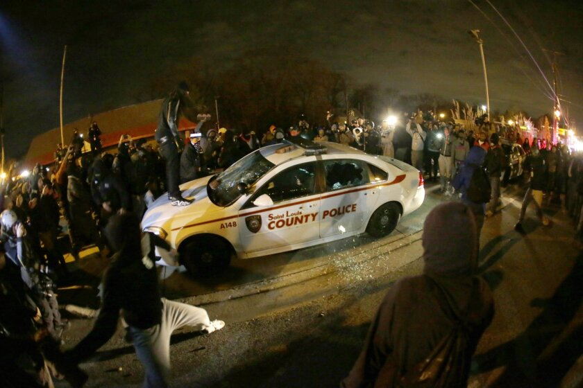 A protester squirts lighter fluid on a vandalized police car in Ferguson, Mo., on Nov. 24.