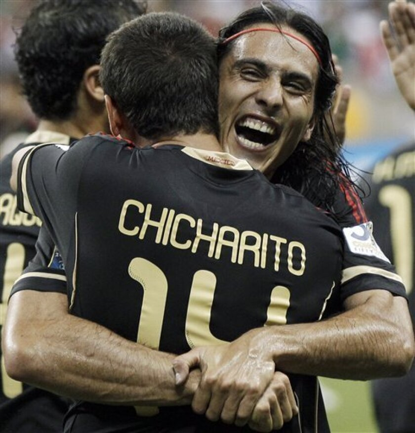 Mexico's Aldo De Nigris, facing camera, congratulates Javier Hernandez for scoring a goal against Honduras during overtime of a CONCACAF Gold Cup semifinal soccer match Wednesday, June 22, 2011, in Houston. (AP Photo/David J. Phillip)