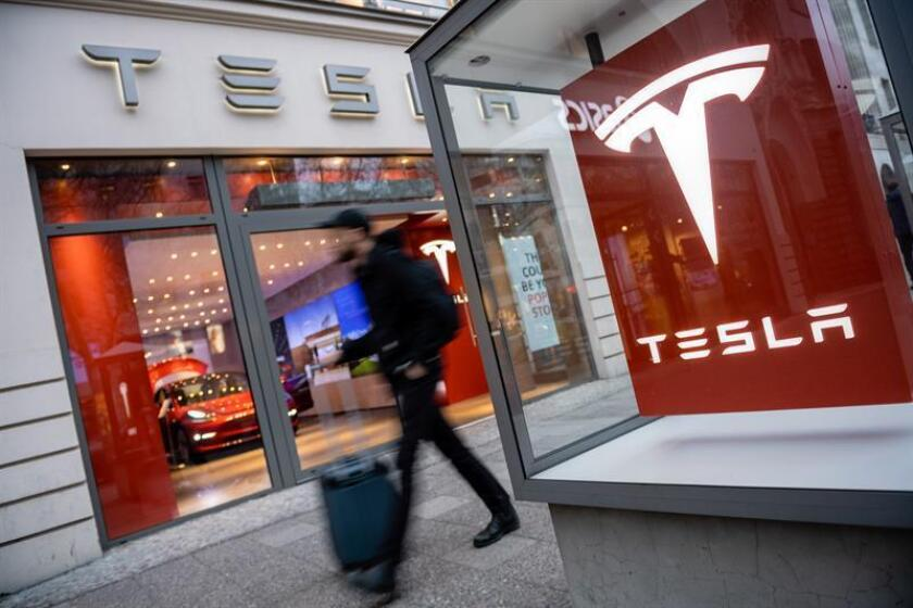 Un hombre camina junto a un sala de exposición de la compañía de vehículos Tesla. EFE/Archivo