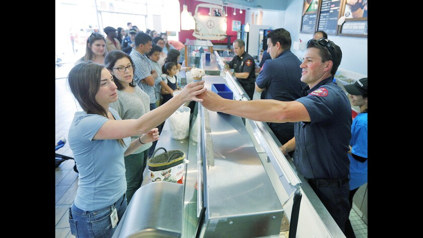 Burbank Firefighter Mike Carey hands Kayla Mackey, of Los Angeles, an ice cream cone at Ben & Jerry's in Burbank on Tuesday, April 10, 2018. The Burbank Fire Department will be handing out single scoops of ice cream as part of the 40th annual Ben & Jerry's Free Cone Day. As well, people can donate to the Muscular Dystrophy Association.