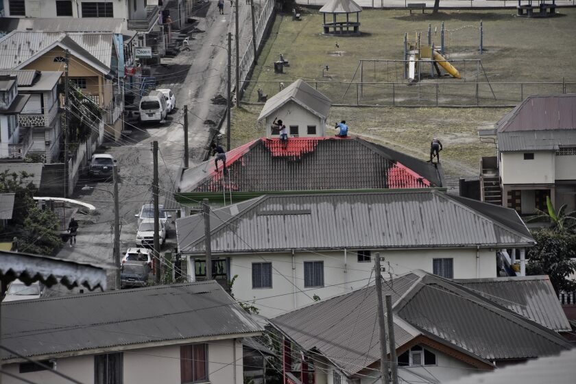 People clean volcanic ash from the red roof of a home.