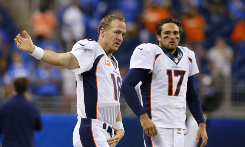 "FILE - In this Sept. 27, 2015, file photo, Denver Broncos quarterbacks Peyton Manning (18) and Brock Osweiler (17) get ready for the Broncos' NFL football game against the Detroit Lions in Detroit. Osweiler gets his first NFL start in his fourth pro season, on Sunday against the Chicago Bears. Manning promises not to ""be in his ear"" all the time, but rest assured he will have some input. (AP Photo/Rick Osentoski, File)"