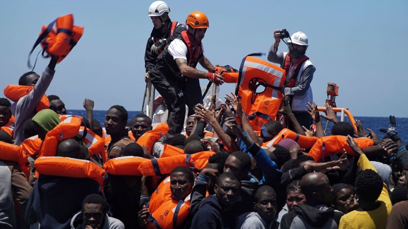 Rescue workers disembark migrants from a dinghy in the Mediterranean Sea.