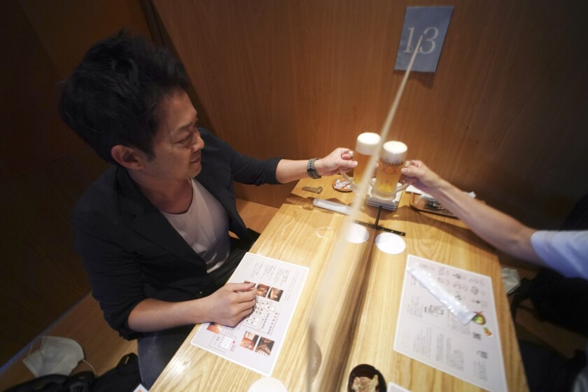 """Customers drink a toast through plastic partitions at Kichiri, an """"izakaya"""" restaurant at Shinjuku district in Tokyo Thursday June 4, 2020. At the restaurant, customers pass through a gate to get whole-body disinfectant smoke, follow a mobile map to their tables and order from tablets with sensors allowing touchless operation. Seats are divided with plastic partitions and dishes delivered with plastic covers. (AP Photo/Eugene Hoshiko)"""