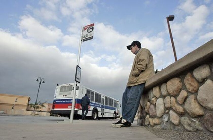 Matt Sasena waited Friday at Santee Town Center for the 834 bus, which is one of nine routes that Metropolitan Transit System officials are targeting for elimination. (Eduardo Contreras / Union-Tribune)