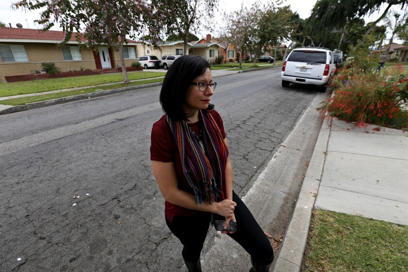 Beatriz Paez, 34, holding a broken phone on the 10400 block of San Juan Avenue in South Gate, where her cellphone was snatched and tossed during a reported federal law enforcement operation she had been recording.