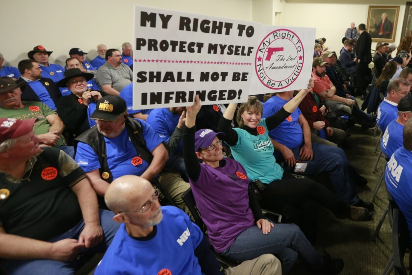 Gun rights protesters hold signs  at the Capitol in Richmond, Va.