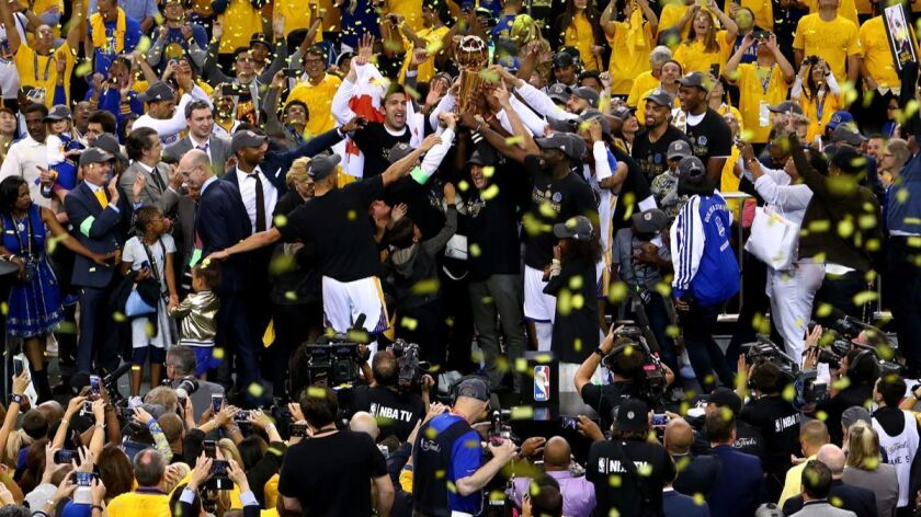 The Golden State Warriors celebrate after defeating the Cleveland Cavaliers, 129-120, in Game 5 to w