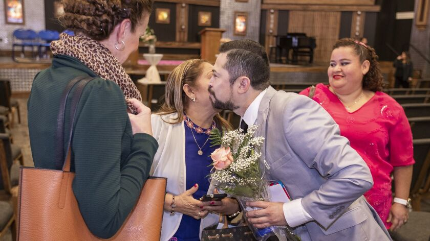 Miguel Rosado, 39, gets a kiss from his mother Ana Zelia Gonzalez following a pinning ceremony on Th
